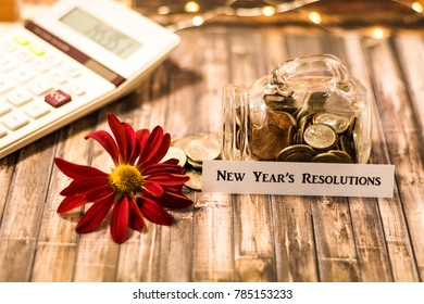 New Year's Resolution money jar savings motivational concept on wooden board