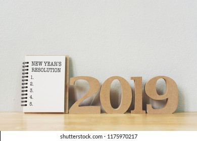 New year's resolution on a notebook and wood number 2019 on wood table, Copy space