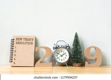 New year's resolution on notebook and wood number 2019 with clock and christmas tree on wood table and copy space