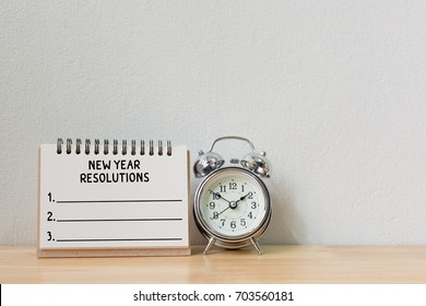New year's resolution on a notebook and alarm clock on wood table, Copy space