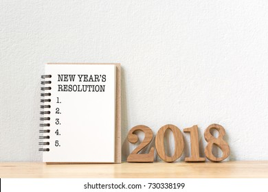 New year's resolution on a notebook and wood number 2018 on wood table, Copy space