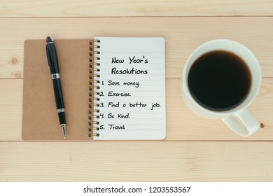 New Year's Resolutions list on notepad with pen and cup of coffee