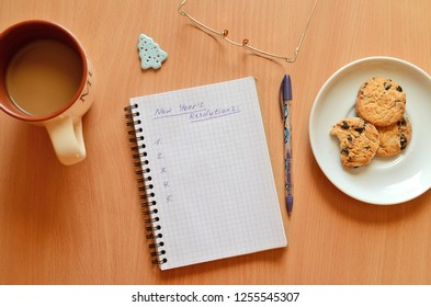 New year's resolutions on a notebook on a wooden table with glasses, cookies, cup of coffe, a blue Christmas tree and a purple pen