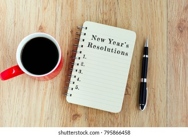 New Year's Resolutions text on notepad with pen and a cup of coffee, wooden background