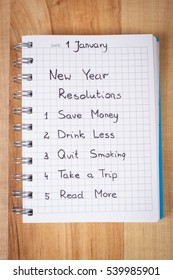 New years resolutions written in notebook, save money, drink less, quit smoking, take trip, read more
