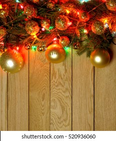New Year`s top border, frame from Christmas tree fir branches, golden pine cones, balls, garland lights on vertical light wooden desk table background. Big copyspace for holiday congratulations.