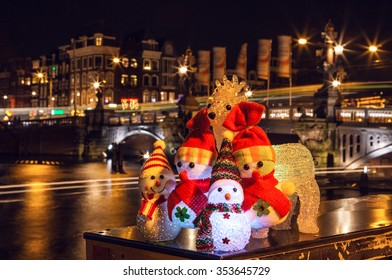 New Year's toys snowmen and deer pose against night canals of Amsterdam.