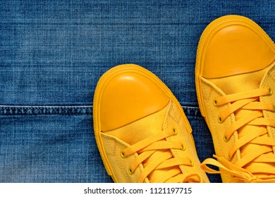 new yellow gym shoes with laces on a blue jeans background with the stitched line closeup