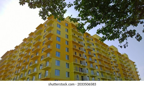 New yellow orange color residential building with green tree. Prices for purchase, sale and rental of real estate. Inexpensive flat. Comfortable housing. Cityscape. City living. Windows and balcony.