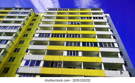 New yellow residential building. Rising price for purchase, sale, rental of real estate. Inexpensive apartments. Construction industry. Cityscape. City living. Windows and balcony. Property. Blue sky.