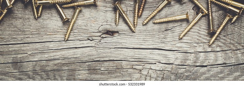 new yellow screws on the wooden table background