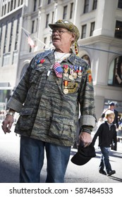 NEW YORK - 11 NOV 2016: A vet wearing a camouflage jacket with medals marches in the annual Americas Parade United War Veterans Council UWVC on 5th Avenue on Veterans Day in Manhattan.