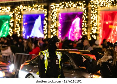 New York, New York - 12/24/2018 : NYPD police officer assisting the crowd in Manhattan while the city is lit up during Christmas time.