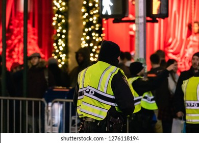 New York, New York - 12/24/2018 : NYPD police officers directing crowds in Manhattan while the city is lit up during Christmas time.
