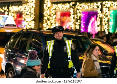 New York, New York - 12/24/2018 : NYPD police officer in Manhattan while the city is lit up during Christmas time.