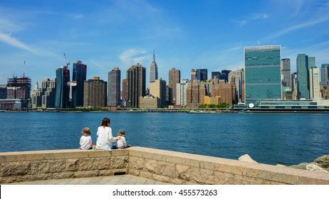 New York, New York - 15 July 2016: Mother with two children at Gantry Plaza State Park in Long Island City spending quality time overlooking the Manhattan Skyline in New York City.