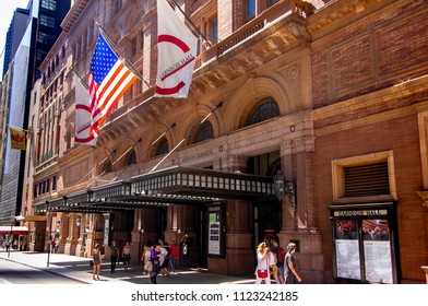 New York, NY—June 16, 2018; pedestrians walk in front of covered entrance to brick landmark Carnegie Hall with national and corporate flags displayed