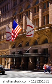 New York, NY—June 16, 2018; pedestrians and traffic pass by the awning covered entrance to the yellow brick Carnegie Hall building with flags displayed in Manhattan