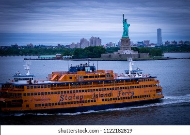 New York, NY—June 23, 2018; yellow and blue Staten Island Ferry passing in front of Statue of Liberty during an overcast morning.