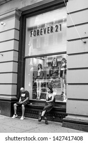 New York, 6/15/2019: A couple of people are sitting against a window of a Forever 21 store in SoHo.