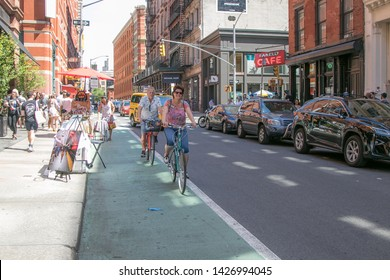 New York, 6/15/2019: Couple that seems in their late 50s are enjoying a stroll on bicycles in SoHo.