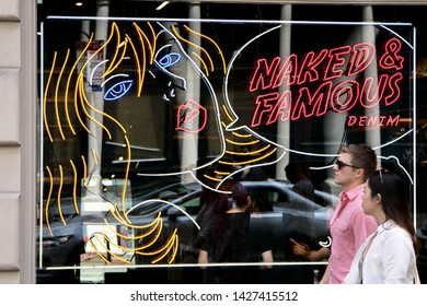 """New York, 6/15/2019: People walk by a """"Naked and Famous Denim"""" store in SoHo."""