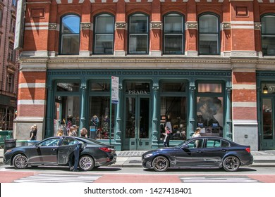 New York, 6/15/2019: Two vehicles are parked in front of a Prada store in SoHo.