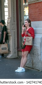 New York, 6/15/2019: Unidentified young lady in a red dress taks on the phone while leaning against a building wall and holding a shopping bag from Bloomingdale's.