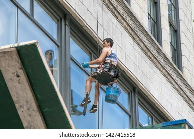 New York, 6/15/2019: Window washer at work while being suspended off a building in SoHo.