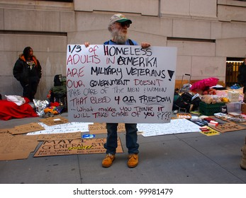 NEW YORK - APR 13: An Occupy Wall Street activist hold a sign on Wall Street April 13, 2012 in New York City, NY. Protesters continued their months-long demonstration against the financial system.