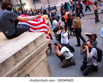 NEW YORK - APR 16: Photographers photograph an unidentified Occupy Wall Street activist holding an upside down American Flag at Federal Hall on Wall Street April 16, 2012 in New York City, NY.