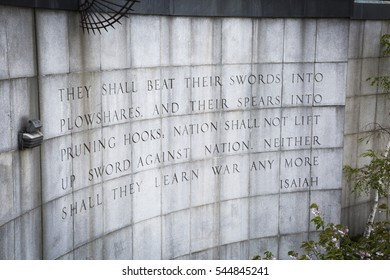 NEW YORK - APR 30 2016: The Bible verse from Isaiah 2:4 inscribed into the granite wall across from the United Nations building in Ralph Bunche Park across 1st Avenue on the East side of Manhattan.