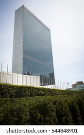 NEW YORK - APR 30 2016: The United Nations building including the line of flag poles and bushes that surround the entrance of the property on 1st Avenue at 43rd St on the East side of Manhattan.