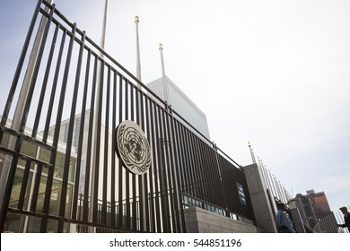 NEW YORK - APR 30 2016: The gold plaque with the United Nations emblem on the metal security fence that surrounds the front of the building on 1st Avenue at 43rd St on the East side of Manhattan.