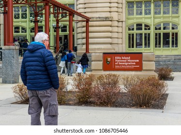 New York - April 10, 2018 : An elderly man reading Elis board on Elis island National Museum of Immigration