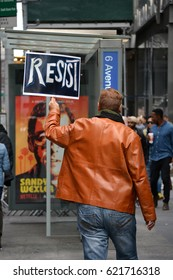 New York, New York. - April 15,, 2017: People carrying signs protesting President Trump at the Tax March in Manhattan in 2017 in New York City.