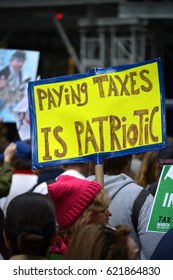 New York, New York. - April 15, 2017: People carrying signs protesting President Trump at the Tax March in Manhattan in 2017 in New York City.