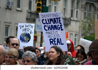 New York, New York. - April 22, 2017: People carrying signs as they participate in The March for Science in Manhattan in 2017 in New York City.
