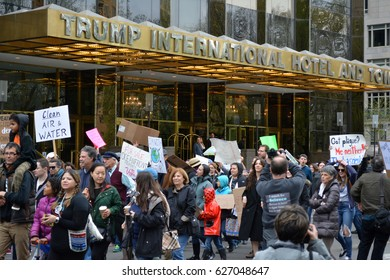 New York, New York. - April 22, 2017: People carrying signs passing by the Trump International Hotel as they participate in The March for Science in Manhattan in 2017 in New York City.