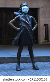NEW YORK, NEW YORK - APRIL 22, 2020: The 'Fearless Girl' statue by Kristen Visbal in front of the New York Stock Exchange wearing a surgical face mask during the COVID-19 coronavirus pandemic.