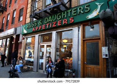 NEW YORK - APRIL 6: Customers eat their food outside of the family-owned Russ & Daughters, a landmark appetizing shop founded in 1914, in New York City on April 6, 2011.