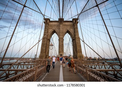 NEW YORK - AUGUST 26, 2017: Tourists and locals fight for space on the crowded pedestrian walkway leading across the Brooklyn Bridge at dusk.