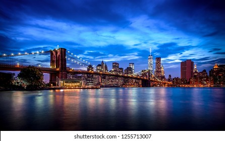 New York blue hour with blue sky in the background and blue sky reflections in the water in the foreground.