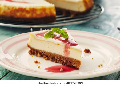 new york cheesecake with cherry sauce on a plate on a blue wooden table, full cake in background