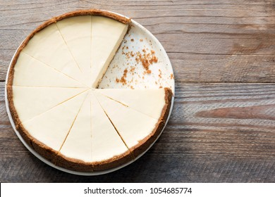 New York Cheesecake or Classic Cheesecake sliced on rustic wood, top view with copy space for text