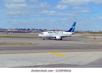 NEW YORK CIRCA APRIL 2018. WestJet plane at airport, a Canadian low cost airline airliner illustrates the global trend of lower budget airlines aiming to take market share away from larger peers