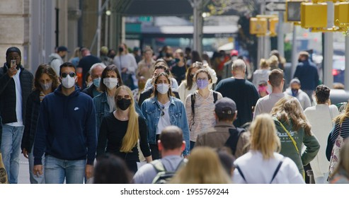 NEW YORK - CIRCA APRIL 2021: Crowd of people wearing masks walking street in Manhattan downtown during Covid 19 coronavirus pandemic