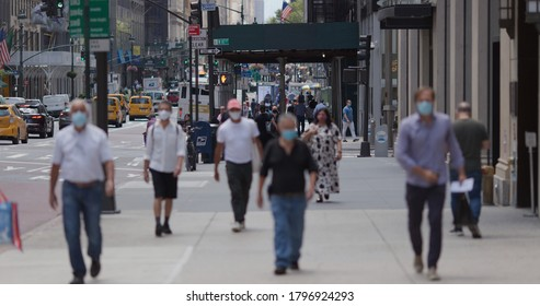 NEW YORK - CIRCA AUGUST 2020: Crowd of people wearing a mask walking street during covid 19 coronavirus pandemic