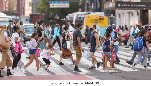 NEW YORK - CIRCA AUGUST 2021: Crowd of people walking crossing street in Manhattan midtown some wearing masks during Covid 19 pandemic