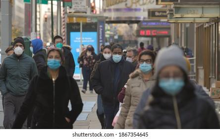 NEW YORK - CIRCA DECEMBER 2020: Crowd of people walking street wearing masks during covid 19 pandemic